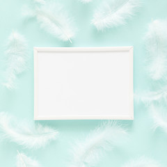 White feathers, photo frame on pastel blue background. Flat lay, top view, copy space, square