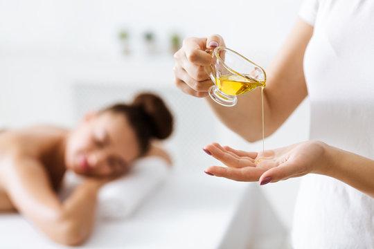 Masseur putting aroma oil on hand, preparing for massage