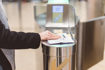 Electronic Boarding pass and passport control in the airport - hand with boarding pass at the turnstile. Wall mural