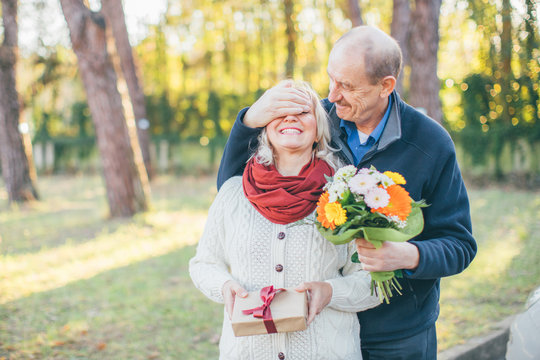 Happy elderly man gives his lady flowers while covering her eyes with palm, she have some present for him - Valentine's Day celebrating, love and getting old together concept.