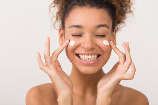 Laughing girl applying moisturizing cream on her face
