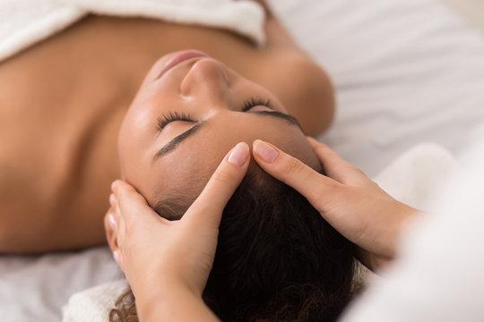 Woman enjoying anti aging facial massage in spa salon