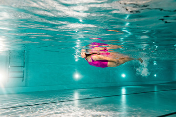 woman swimming in blue water in swimming pool