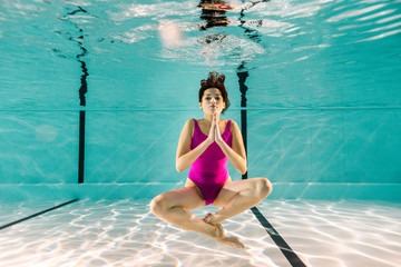 attractive woman posing underwater in swimming pool