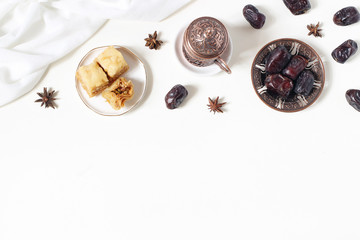Ramadan Kareem greeting card, invitation. Bronze plate with dates fruit, baklava pastry, coffee cup, anise stars on white table. Iftar dinner. Eid ul Adha banner background. Muslim flat lay, top view.