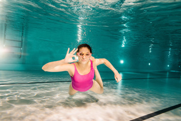 woman in googles showing ok sign while diving underwater