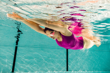 focused woman diving in googles in swimming pool