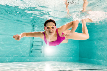 smiling woman in googles and pink swimsuit diving underwater in swimming pool