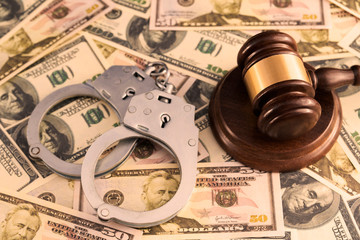 the judge's gavel, the iron handcuffs for detention of criminals on the background of banknotes of American dollars. financial crime.