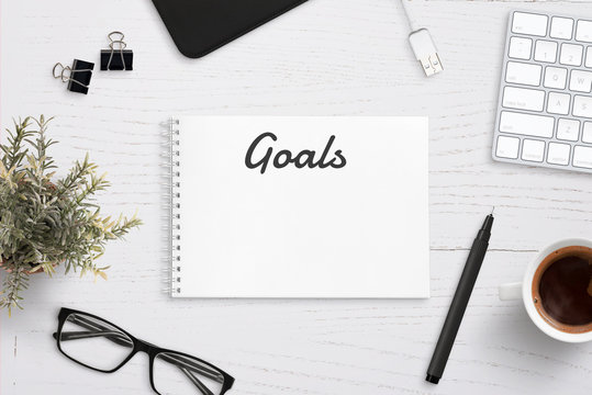 Creating goals list on notepad on office desk surrounded with office supplies. White wooden work desk.