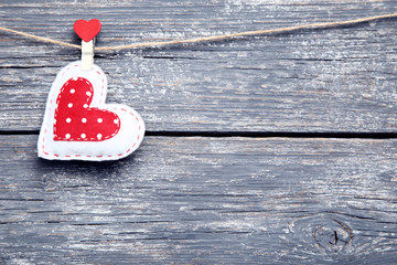 Fabric heart hanging on grey wooden background