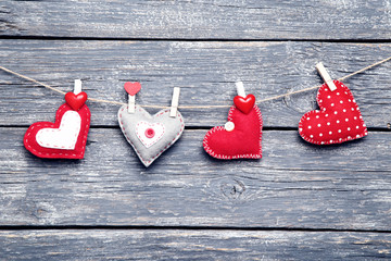Fabric hearts hanging on grey wooden background