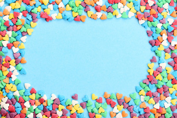 Colorful heart shaped sprinkles on blue background