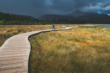 Tourist walking on the wooden path. Northern Ireland. Mighty mountains background. Rainy cloudy sky in grey tints. The backpacker on the trail. Hiking among the wild environment. Outdoor activity.