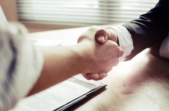 close up hand of two business people shaking hands after successful job interview in modern meeting room at office, home loan contract, partnership, teamwork and business contract concept