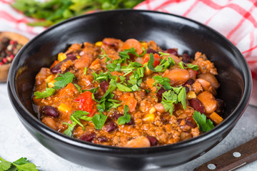 Chili con carne from meat and vegetables on stone table close up.