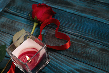 red roses candle and heart with red ribbon on blue background