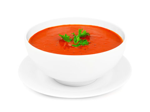 Homemade tomato soup in a white bowl with saucer. Side view isolated on a white background.