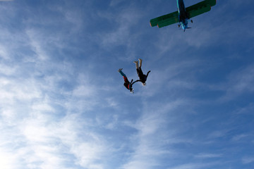 Two skydivers are flying in the blue sky.