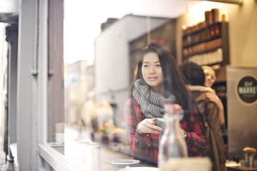Asian woman looking out of a cafe window