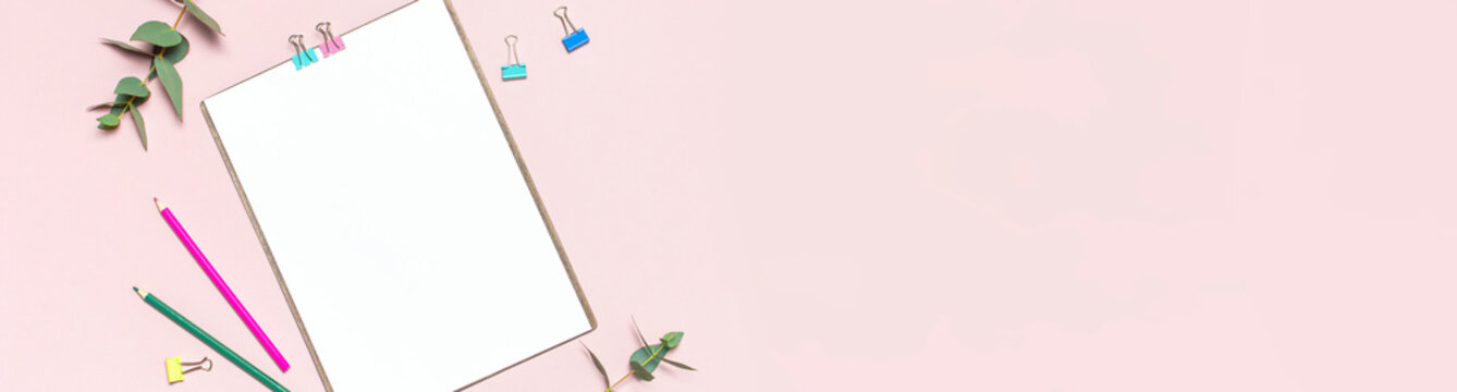 Flat lay clipboard with blank paper, colour pencils, clips, eucalyptus branches on pink background. Top view female office workspace minimal mock up template concept copy space Feminine floral desktop
