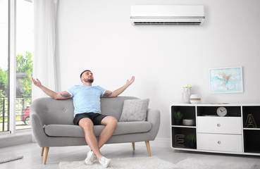 Young man relaxing under air conditioner at home