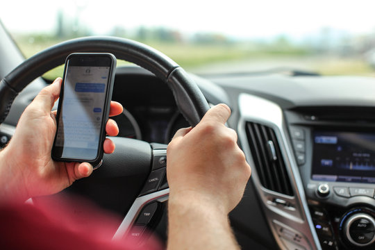 Man checking his text messages while driving. Dangerous texting in car concept.