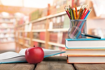 Stack of colorful books and fresh apple