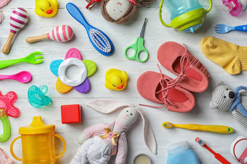 Flat lay composition with baby accessories and toys on light wooden background
