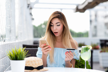 Girl cafe in summer. Pay breakfast and lunch with plastic card by phone via Internet application. Emotion of surprise, shocked valuable product. Concept of misunderstanding confusion big write-off.
