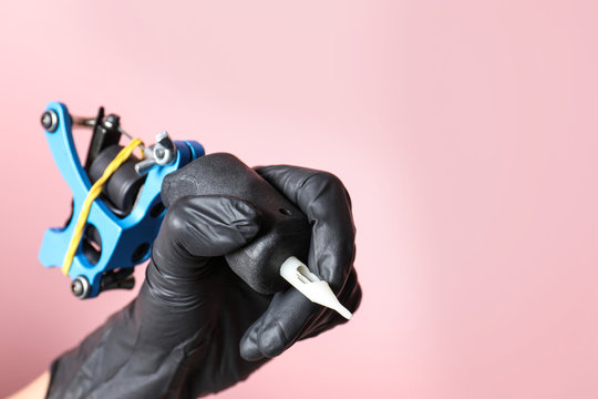 Professional tattoo artist with machine on color background, closeup. Space for text
