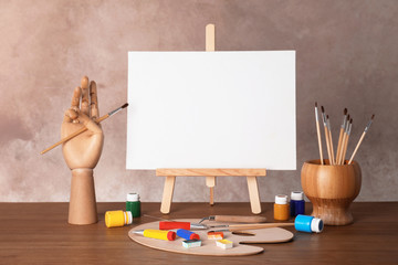 Wooden easel with blank canvas board and painting tools for children on table near color wall