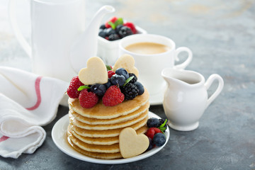 Valentines day breakfast, pancakes with hearts and fresh berries topping