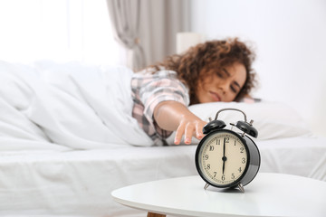 Young African-American woman turning off alarm clock at home. Bedtime