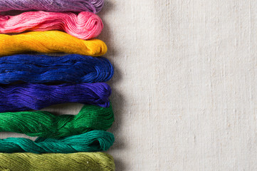 Thread embroidery, different threads on the cotton background.
