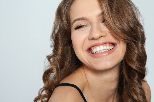 Portrait of beautiful young woman with shiny wavy hair on color background, closeup