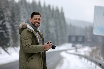 Male photographer with camera on snowy road, space for text. Winter vacation