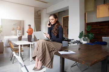 Young businesswoman making a call while sitting on office desk and working
