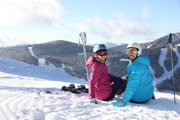 Happy couple with ski equipment sitting on snowy hill in mountains, space for text. Winter vacation