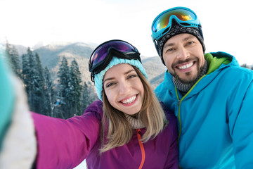 Happy couple taking selfie during winter vacation in mountains