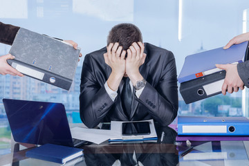 A businessman is closing his face with his hands in working stress assault.