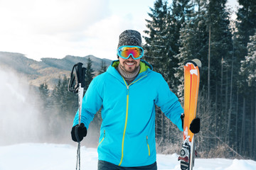 Man with ski equipment spending winter vacation in mountains