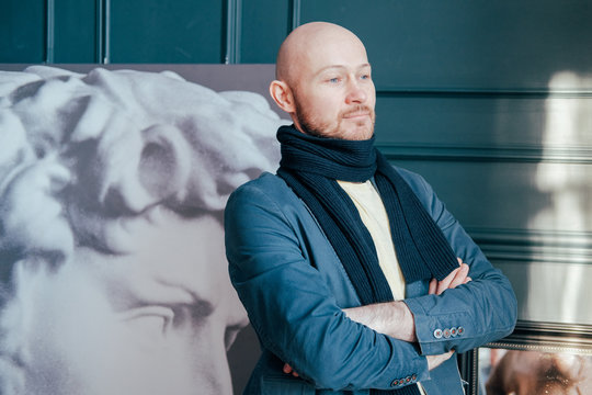 Portrait of attractive adult successful bald man art critic historian with beard in scarf in art gallery