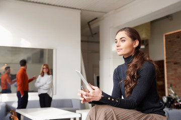 Businesswoman using her digital tablet while sitting in the office and working