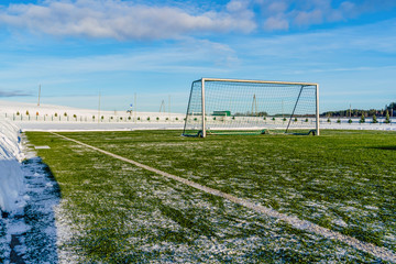 Empty Football (Soccer) Field in the Winter Partly Covered in Snow - Sunny Winter Day