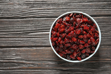 Bowl with cranberries on wooden background, top view with space for text. Dried fruit as healthy snack