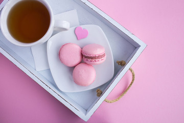 Breakfast with pink macaroons and tea on the white wooden tray on the light pink  background.Top view.Closeup.