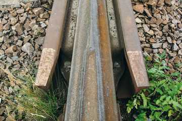 Old rusty railway lines with grey stone chippings lying on the ground outdoors. Natural industrial background texture.