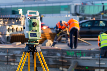 Surveyor equipment (theodolite) on construction site of the airport, building or road with construction machines in background Fototapete
