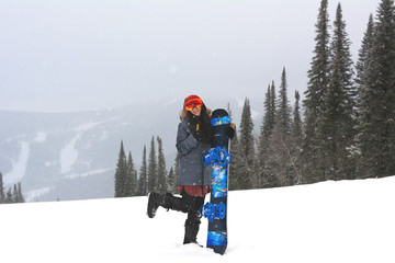 Young smiling stylish snowboarder girl stand ..bending one leg on top of a mountain and holding her snowboard and showing thumb up. Prepearing to ride and searching for her line. Freeride in blizzard.